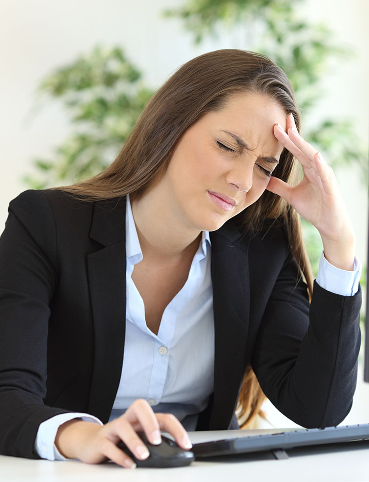 Lady suffering from depression and stress at her desk in the workplace